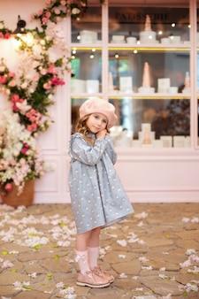 Glückliches kleines mädchen mit langen lockigen haaren in einem blauen kleid und baskenmütze