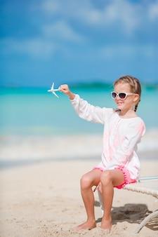 Glückliches kleines mädchen mit spielzeugflugzeug am strand