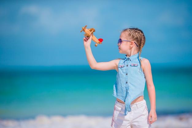 Glückliches kleines mädchen mit spielzeugflugzeug in den händen am weißen sandstrand. kind spielen mit spielzeug am strand