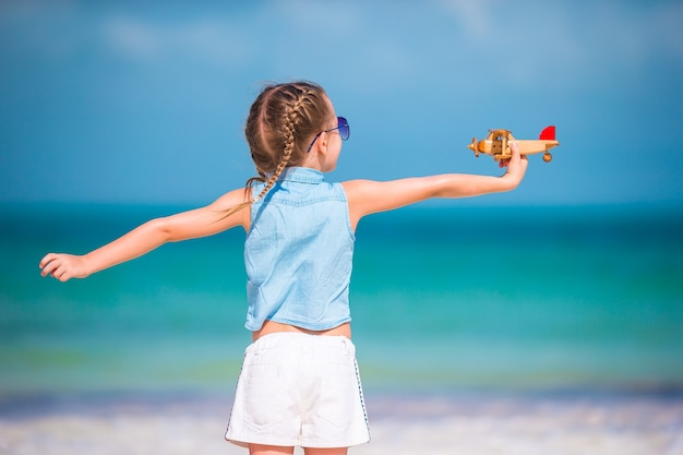 Glückliches kleines mädchen mit spielzeugflugzeug in den händen am weißen sandstrand.