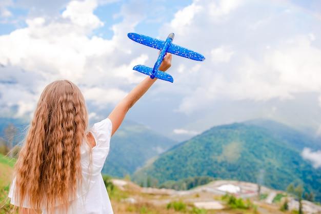 Glückliches kleines mädchen mit spielzeugflugzeug in den händen in den bergen