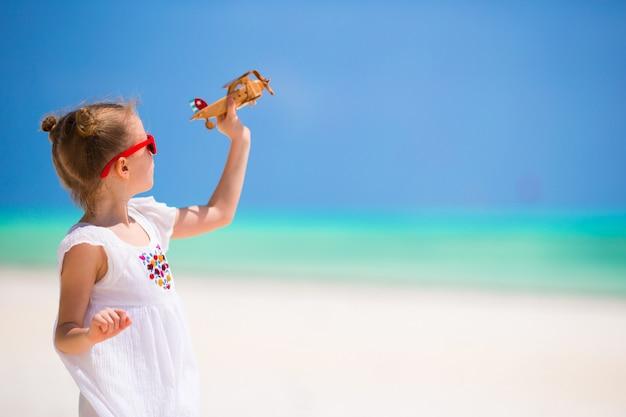 Glückliches kleines mädchen mit spielzeugflugzeug während der strandferien
