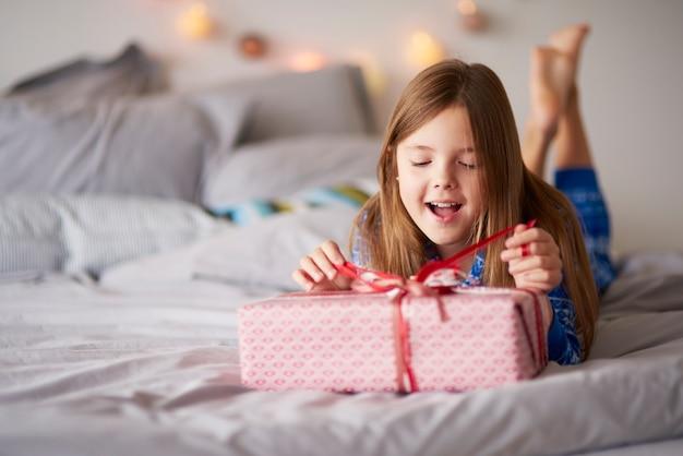 Glückliches kleines mädchen mit weihnachtsgeschenk