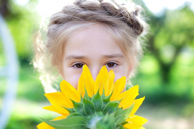 Glückliches kleines mädchen mit zopfhaar mit sonnenblume im sommergarten. kind, das gesicht mit sonnenblume bedeckt. kindheitskonzept. nettes junges blondes mädchen des nahaufnahmeporträts mit großer sonnenblume vor gesicht.
