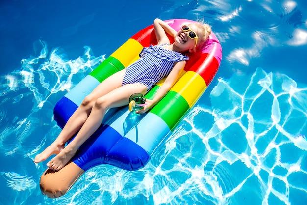 Glückliches kleines mädchen schwimmt im sommer im pool auf einer matratze in form von eisraum für text