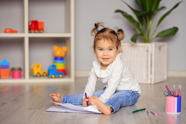 Glückliches kleines mädchen sitzt auf dem boden und zeichnet mit buntstiften auf papier