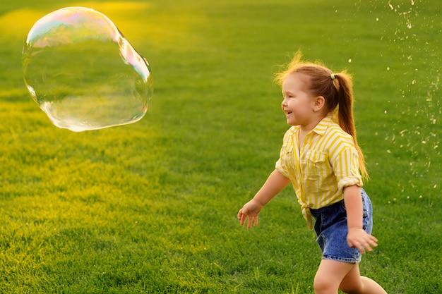 Glückliches kleines mädchen spielt mit seifenblasen im park.