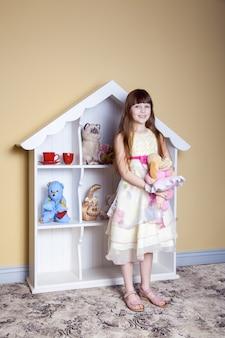 Glückliches kleines mädchen spielt mit spielzeug in ihrem zimmer, lächelt und schaut in die kamera. studioaufnahme.