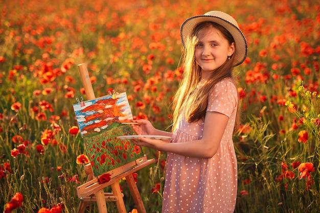 Glückliches kleines mädchen steht im feld der roten mohnblumen und malt auf der leinwand auf einem zeichenständer