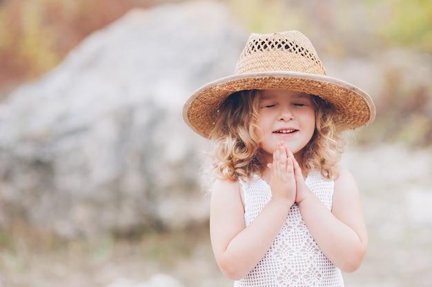 Glückliches kleines mädchen trägt einen hut im freien