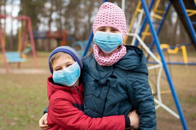 Glückliches kleines mädchen und junge auf spielplatz. kleine kinder in medizinischen masken spielen auf dem spielplatz während der coronavirus-epidemie