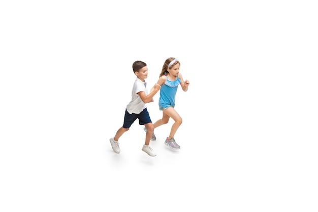 Glückliches kleines mädchen und junge, die auf weiß laufen Premium Fotos