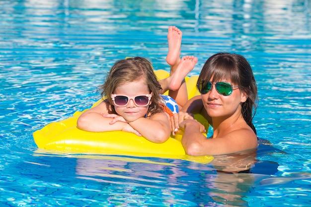 Glückliches kleines mädchen und mutter im pool