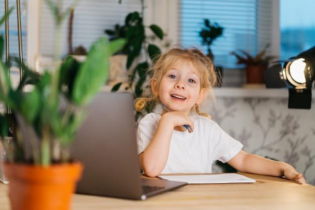 Glückliches kleines mädchen vlogger sitzt am laptop, der kamera betrachtet, lächelt und online-videoanruf-video-blog-aufzeichnung macht.