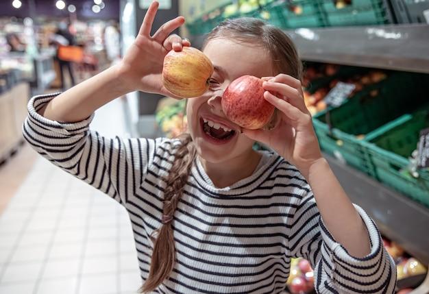 Glückliches kleines mädchen wählt äpfel in einem lebensmittelgeschäft.
