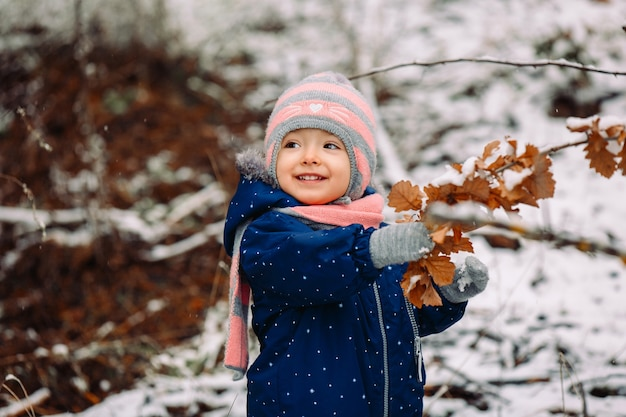 Glückliches kleines mädchen warm gekleidet spielt in einem winterpark und schaut zur seite.