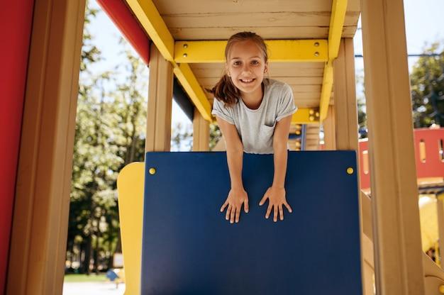 Glückliches kleines mädchen wirft auf spielplatz, kinderstadt auf. kind klettert auf hängebrücke