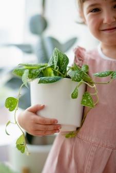 Glückliches kleines mädchen zu hause mit zimmerpflanzen