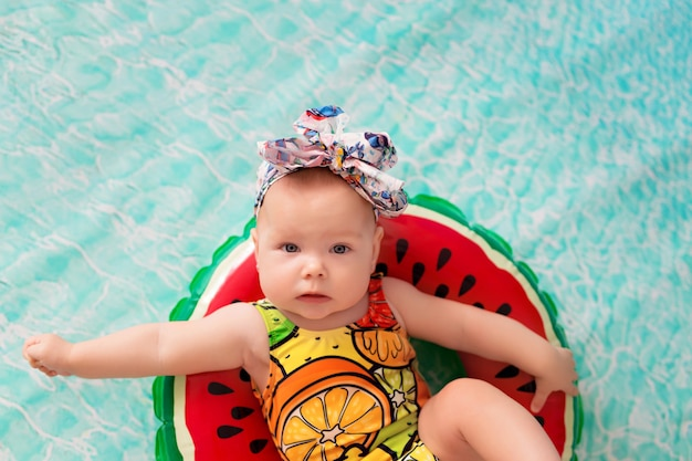 Glückliches kleines mädchenbaby schwimmt im meer in einem rettungsring in der form einer wassermelone