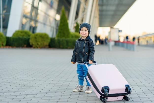Glückliches kleines reisendes mädchen zieht großen koffer zum flughafen.