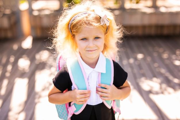 Glückliches kleines schulmädchen mit dem mittagessen, buch und bleistiften. zurück in die schule im freien