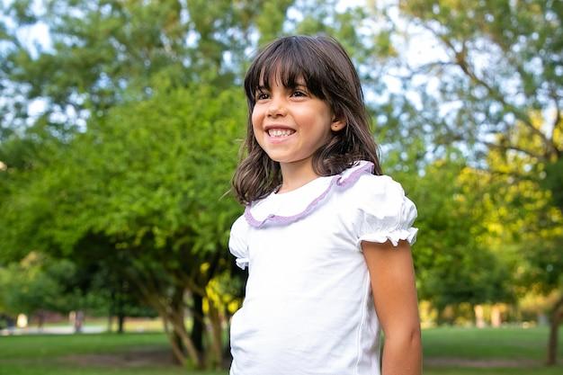 Glückliches kleines schwarzhaariges mädchen, das im stadtpark steht, wegschaut und lächelt. kind, das freizeit im freien im sommer genießt. mittlerer schuss. kindheitskonzept
