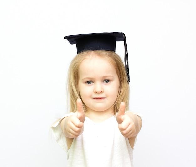 Glückliches kleines studentenmädchen im studentenhut, das daumen oben in lokalisiertem weißem hintergrund zeigt