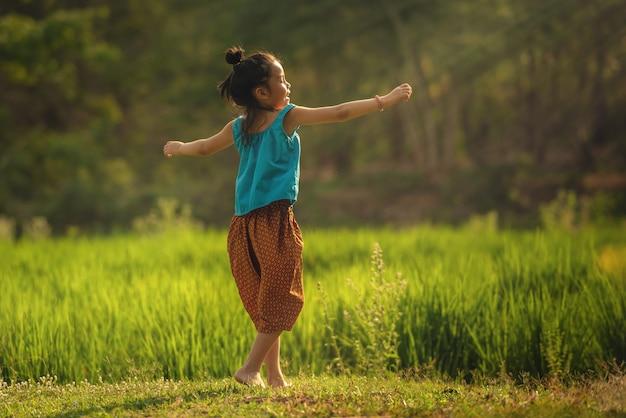 Glückliches kleines süßes asiatisches kindermädchenschwarzes langes haarlächeln genießen, zu spielen und zu tanzen