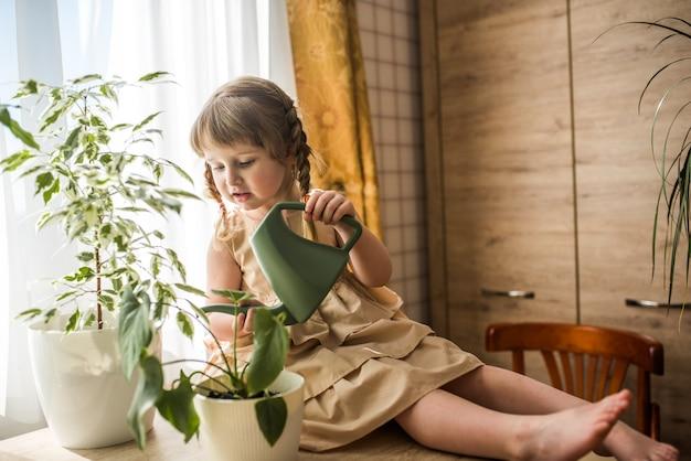 Glückliches kleines süßes baby kümmert sich um zimmerpflanzen. mädchen, das zimmerpflanzen zu hause gießt und besprüht