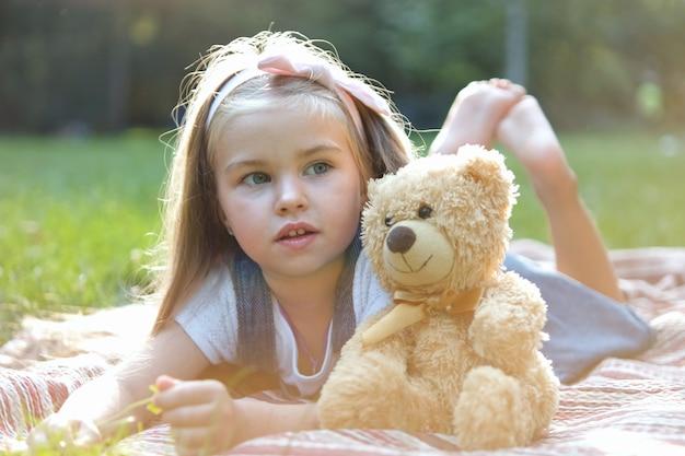 Glückliches kleines vorschulmädchen, das mit ihrem lieblingsteddybärspielzeug draußen im sommerpark spielt.