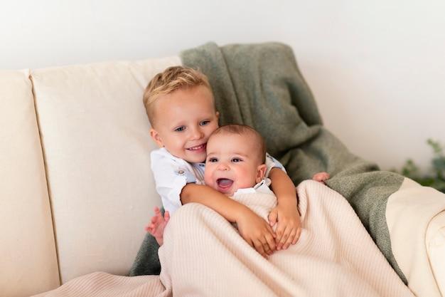 Glückliches kleinkind, das entzückende geschwister umarmt