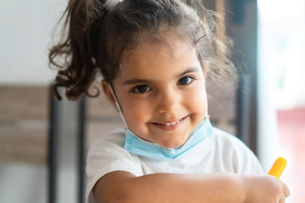 Glückliches kleinkind in der schule mit schützender gesichtsmaske