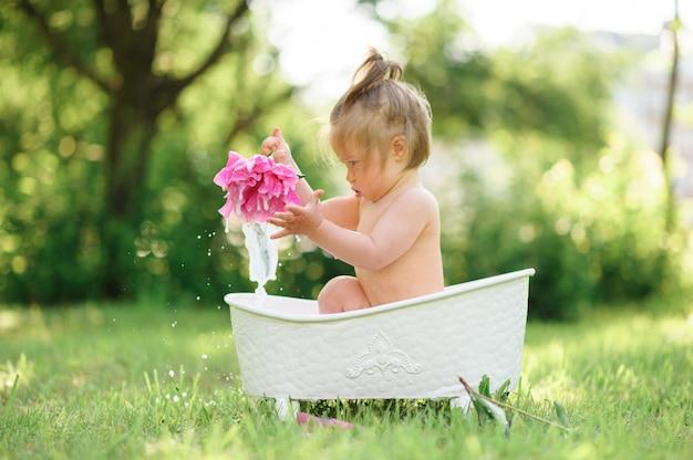 Glückliches kleinkindmädchen nimmt ein milchbad mit blütenblättern. kleines mädchen in einem milchbad auf einem grün. blumensträuße aus rosa pfingstrosen. baby baden. hygiene und pflege für kleine kinder.