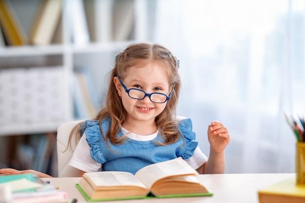 Glückliches kluges kleines mädchen mit brille sitzt am tisch mit buch