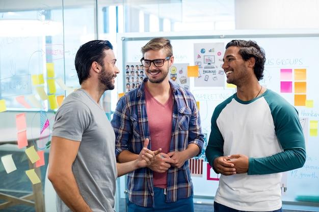 Glückliches kreatives geschäftsteam, das gegen die weiße tafel und haftnotizen diskutiert