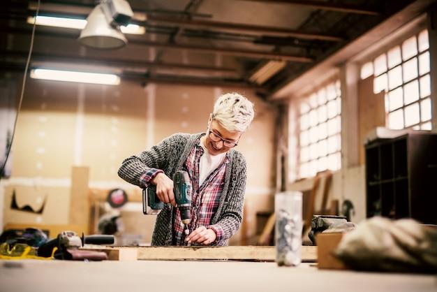 Glückliches kurzes haar weiblich, das mit der elektrischen bohrmaschine in einer großen garage arbeitet