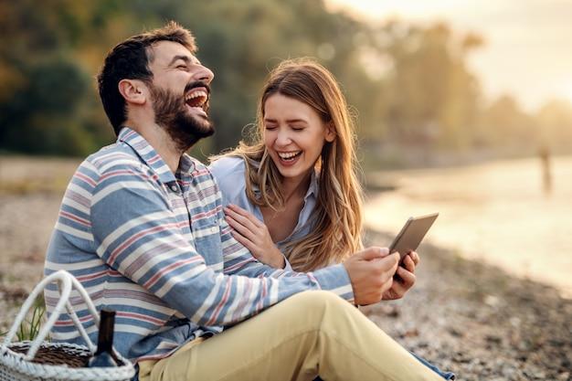 Glückliches lachendes kaukasisches modisches junges paar, das an der küste nahe fluss sitzt und tablette verwendet. mann, der tablette hält. neben dem mann steht ein picknickkorb.