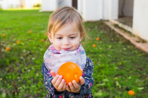 Glückliches lachendes kind, das mit orange spielt