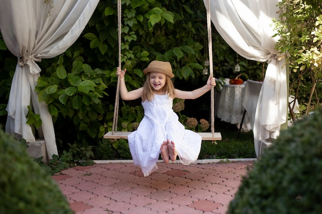 Glückliches lachendes kindermädchen auf schaukel im sommer