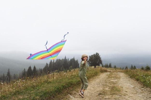 Glückliches lachendes kleines mädchen, das einen bunten drachen fliegt, läuft und springt am nebligen tag in den bergen während des aktiven familienurlaubs. kinder spielen im freien. glückliche kindheit.