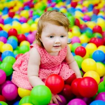 Glückliches lachendes mädchen, das mit spielzeug, bunten bällen im spielplatz, ballgrube, trockenem pool spielt. kleines niedliches kind, das spaß in der ballgrube auf geburtstagsfeier im kinder-vergnügungspark und im spielzentrum innen hat.