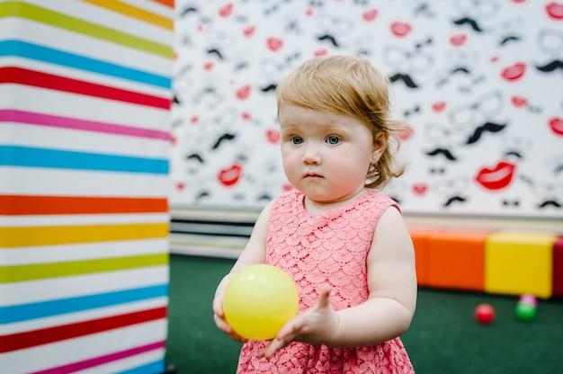 Glückliches lachendes mädchen, das mit spielzeugen spielt, bunte bälle im spielplatz im spielzimmer. kleines niedliches lustiges kind auf geburtstagsfeier im kinder-vergnügungspark und im spielzentrum drinnen.