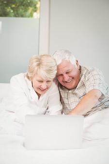 Glückliches lachendes paar bei der anwendung des laptops im bett