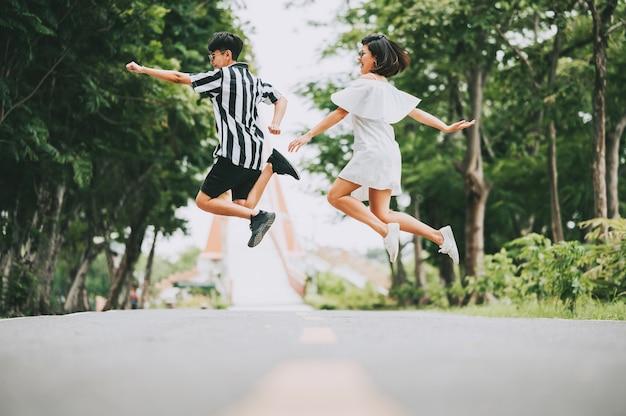 Glückliches lächeln asiatisches lesbisches paar, das vom boden draußen im park springt.