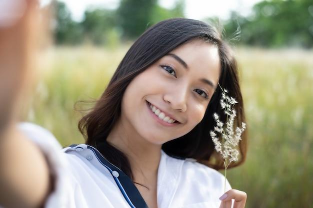 Glückliches lächeln der asiatinnen, das fotos und selfie auf entspannender zeit an der wiese und am gras macht