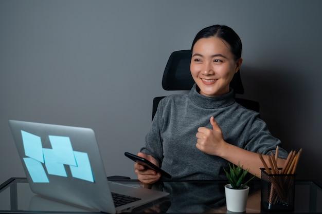 Glückliches lächeln der asiatischen frau beim betrachten des kopierraums, das an einem laptop im büro arbeitet