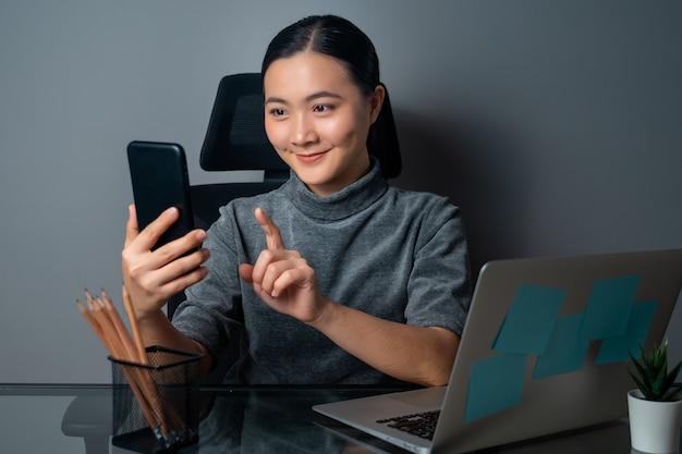 Glückliches lächeln der asiatischen frau unter verwendung des smartphones und arbeiten an einem laptop im büro
