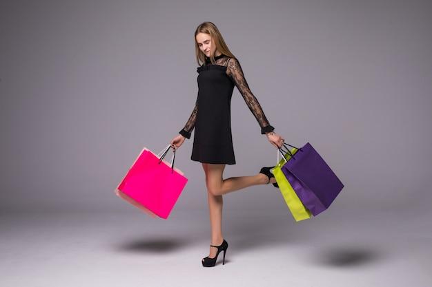 Glückliches lächeln der einkaufsfrau, die einkaufstaschen lokalisiert auf grauem hintergrund hält.