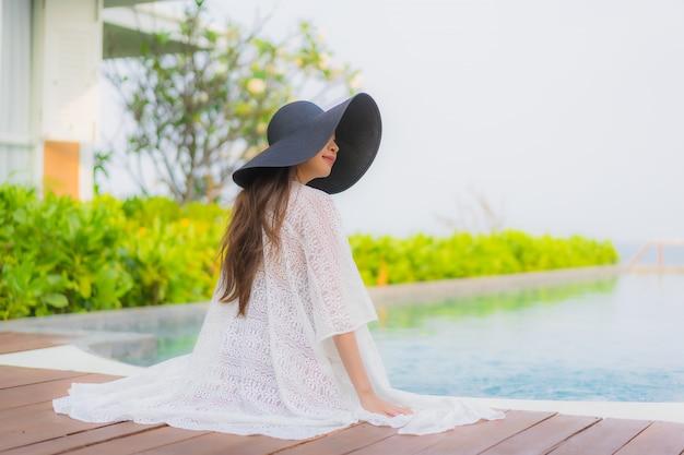 Glückliches lächeln der jungen asiatischen frau des porträts entspannen sich um außenpool