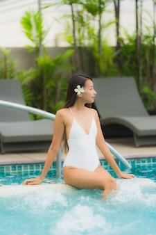 Glückliches lächeln der jungen asiatischen frau des porträts entspannen sich um swimmingpool im hotelerholungsort